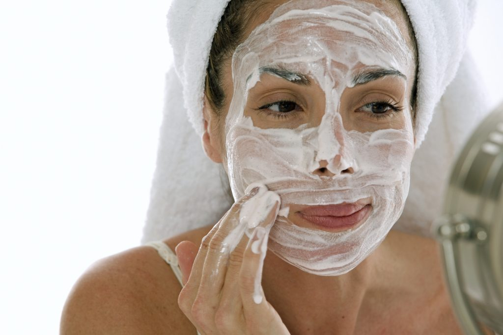 Close-up of a young adult woman applying cleanser to her face