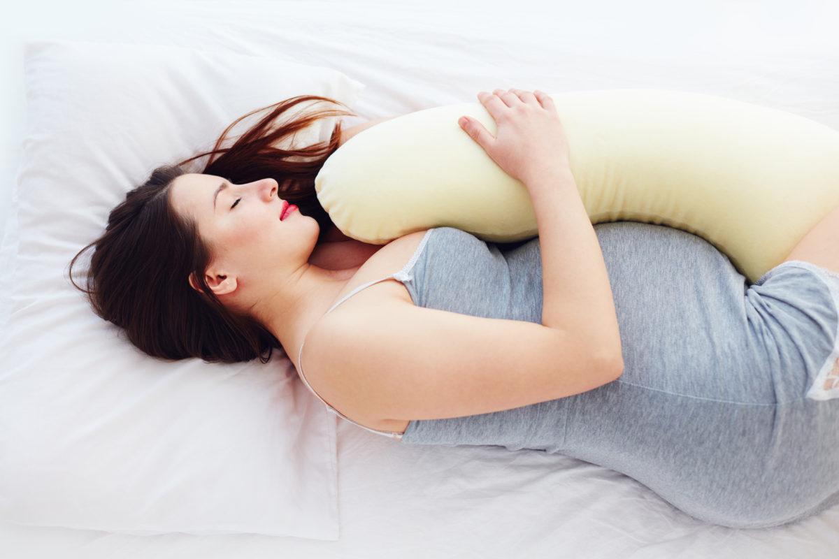 mujer embarazada durmiendo sobre una almohada